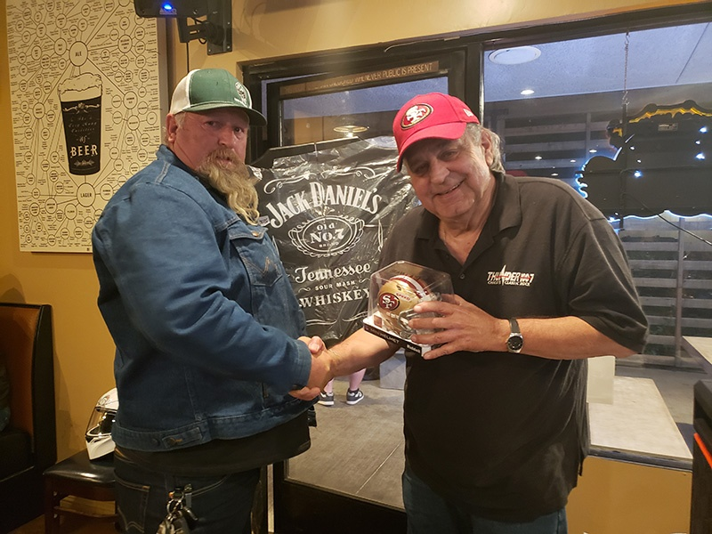 Ron presenting the Thunder grand prize winner with his Jack Daniels dartboard and plus an autograph Joe Staley (#74) mini helmet.